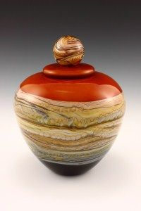 GlassMasters Danielle Gartner and Stephen Blade's Covered Puffy Jar Tangerine with Ball Finial from their Strata Series.