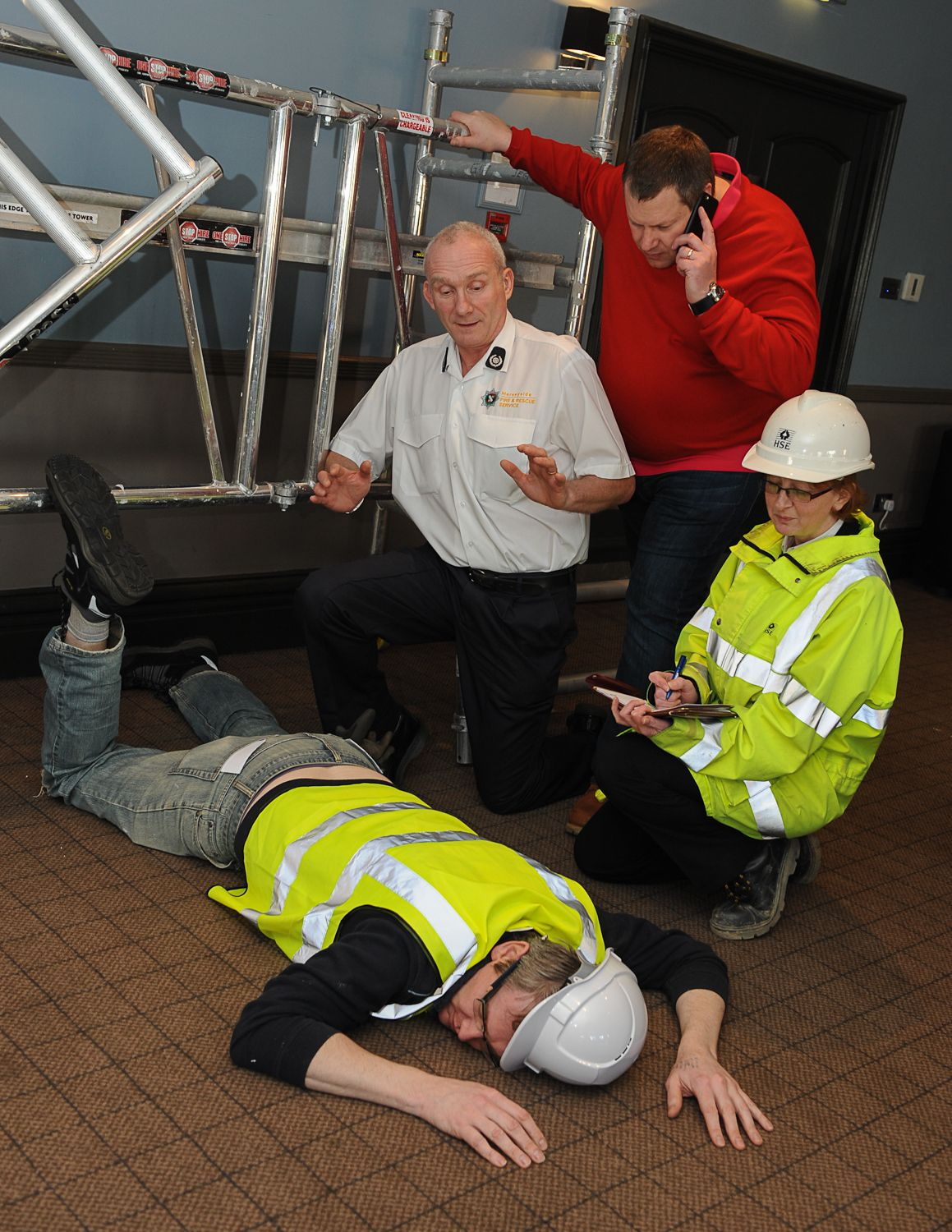 'Mick's' boss 'Pete' (red jumper) attends the scene along with a firefighter and a HSE inspector. 'Pete' knows he will have questions to answer about why 'Mick' was allowed to carry out the work when the tower was unsafe.