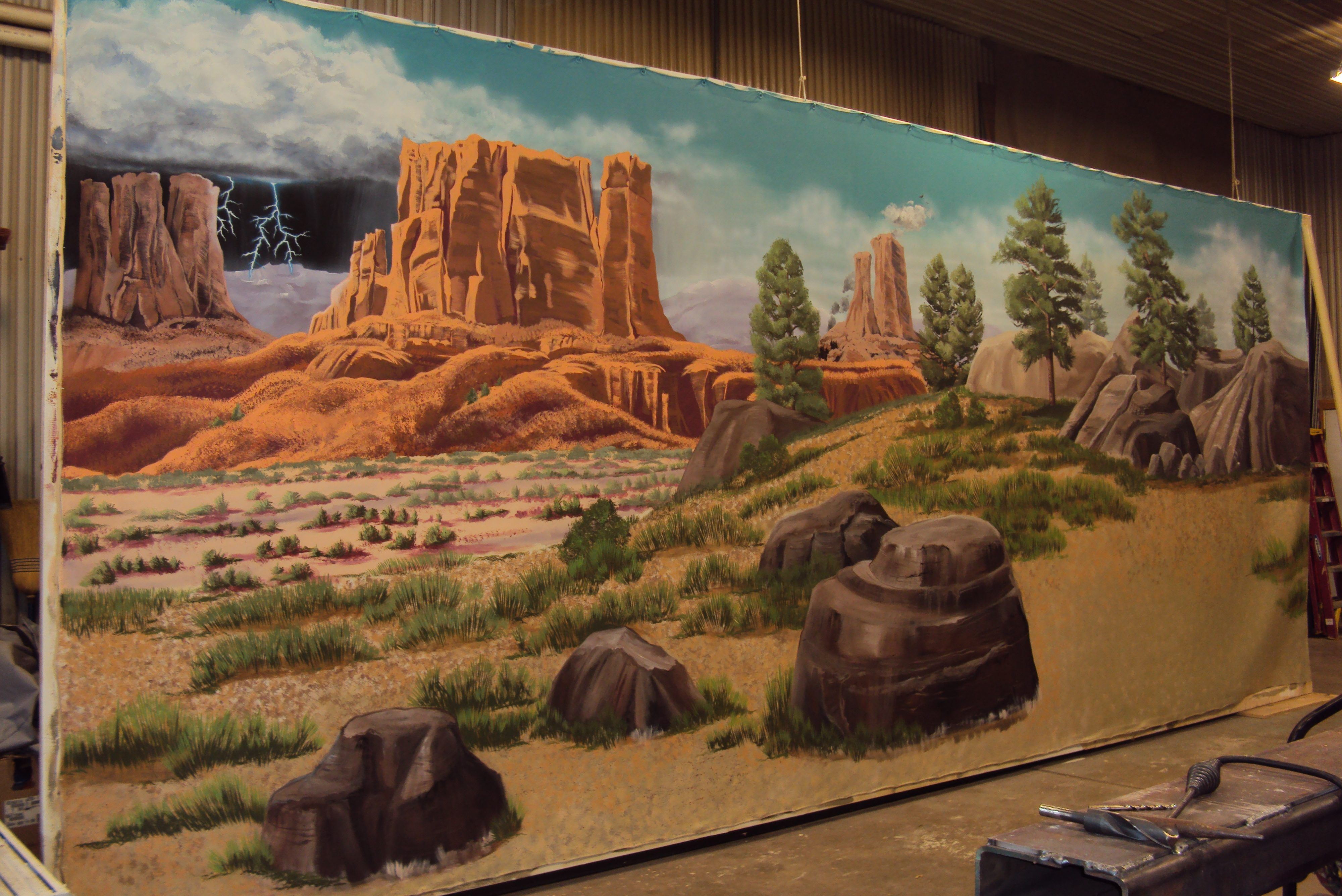10'x30'mural Latex and acrylic paints with sealer on canvas.  This mural is a backdrop in the Bonanza Shooting Gallery.