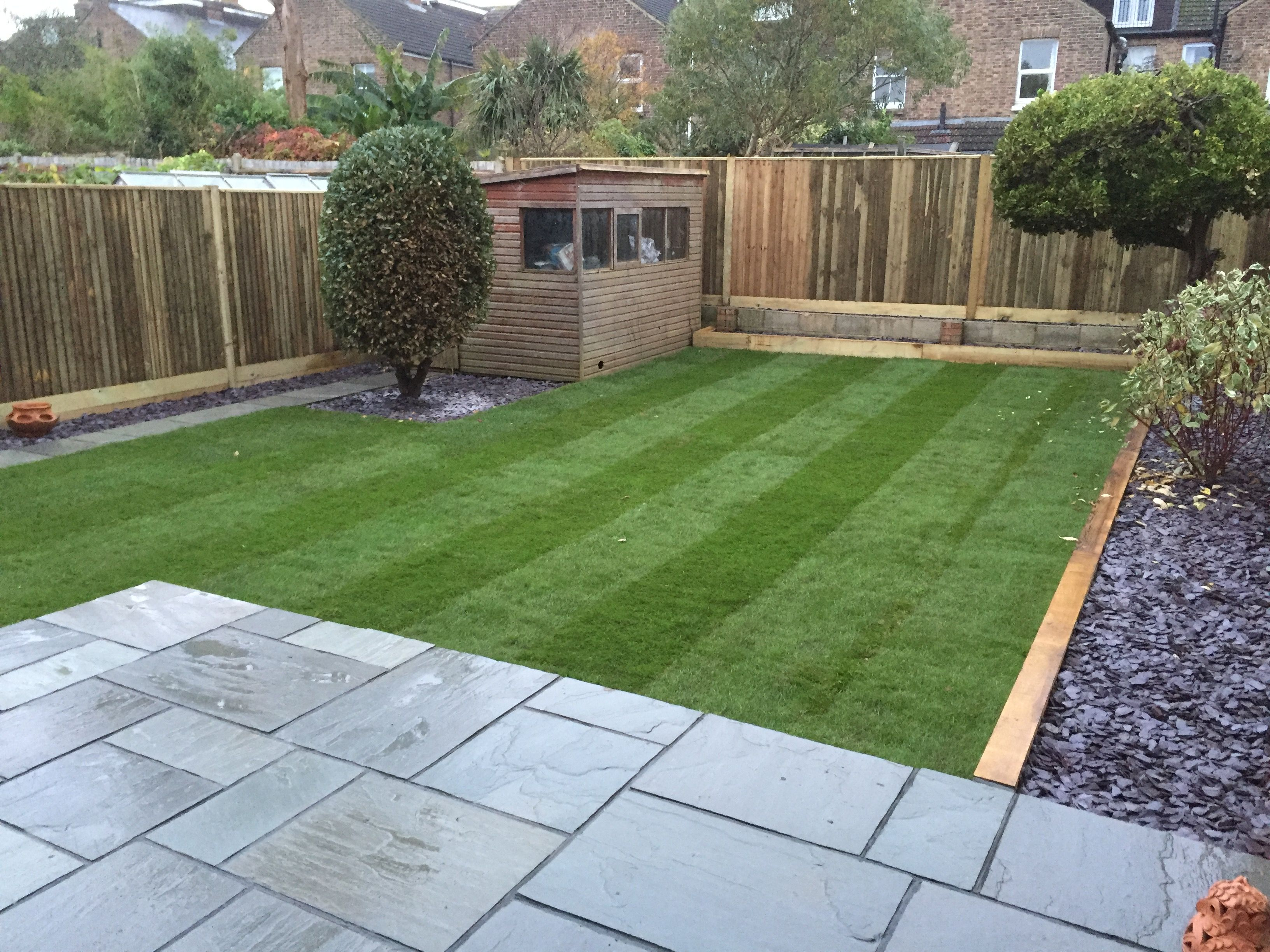 Grey sandstone terrace sleeper borders mulched with slate Low maintenance garden border ideas