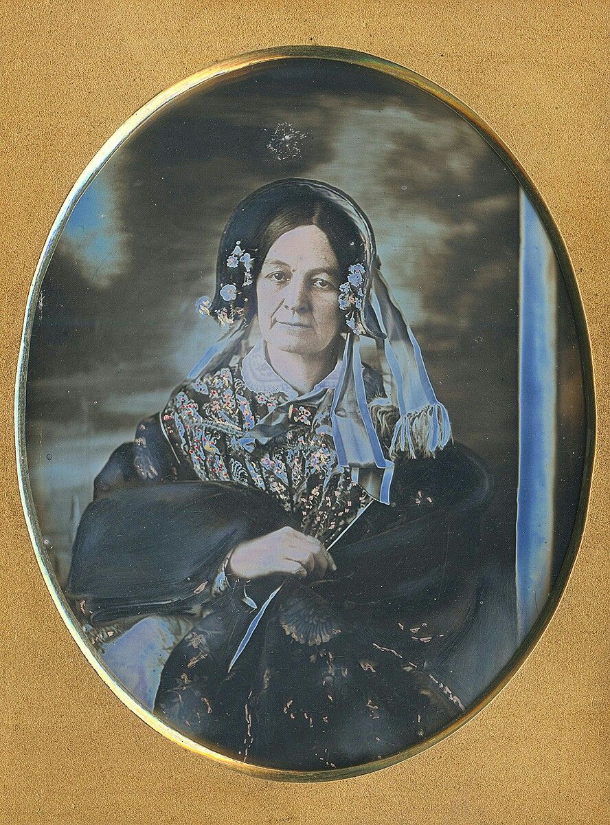 A quarter plate of an older female with vivid brown eyes and softly composed mouth. The broad expanse of light from above and left of the daguerreian's patron provided magical illumination! The vertical blue (actually white) strip of reflector seems too narrow to have successfully softened the shadows. Notice that at the last moment before the lens was uncapped either the operator or an assistant altered the position of the lady's bonnet causing it to become slightly askew.