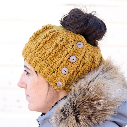 """Would you believe this bun beanie (AKA ponytail hat) is worked in only single crochet and chain stitches? Despite it's simple construction, the """"cabled"""" look of this beanie is sure to dress up even the messiest of messy buns. And the functional bottoms mean that you can pop this puppy on without pulling it over your perfectly tussled hair."""