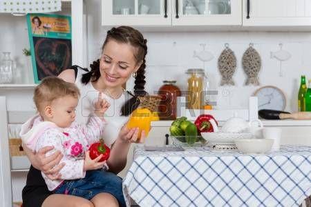 Junge Mutter mit kleinem Kind sitzen am Esstisch in der K?che zu - baby born küche