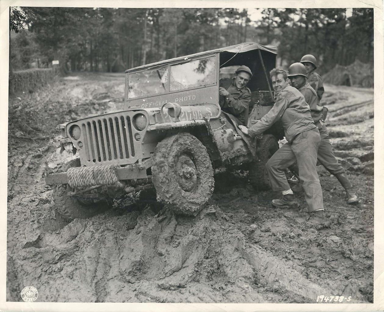 U.S. soldiers work to free jeep mired in the mud of Germany. October 1944