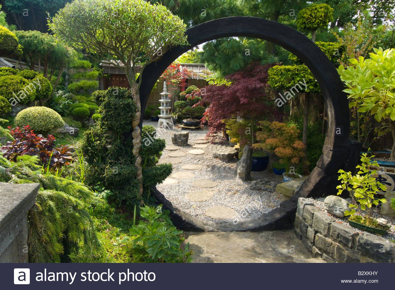 Japanese style garden with moon gate rocks shrubs and ...