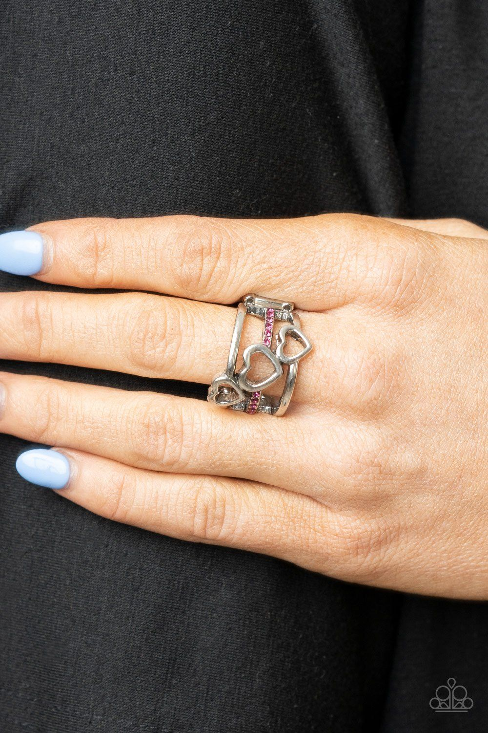 Infused with a row of glittery pink rhinestones, a trio of airy silver hearts slant across three silver bands that layer into a charming centerpiece atop the finger. Features a stretchy band for a flexible fit. Sold as one individual ring.