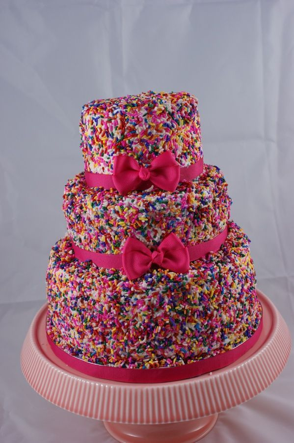 Buttercream cake covered in sprinkles with pink bows for a girls