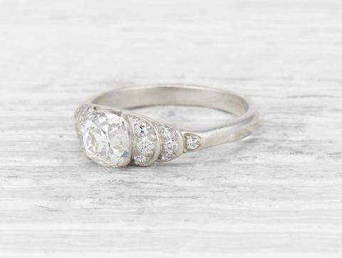 Art Deco engagement ring set with an old mine-cut diamond weighing approximately 1.25 carats with GIA certificate stating the diamond is J color/VS2 clarity. The scalloped step shoulders set with 14 single-cut diamonds. Set in platinum. Circa 1920. The scalloped shoulders on this Art Deco engagement ring are modern and unique. The ring is not short on sparkle too! Learn more about Art Deco rings Diamond and gold mining has caused devastation in areas such as Africa, wreaking havoc on de...