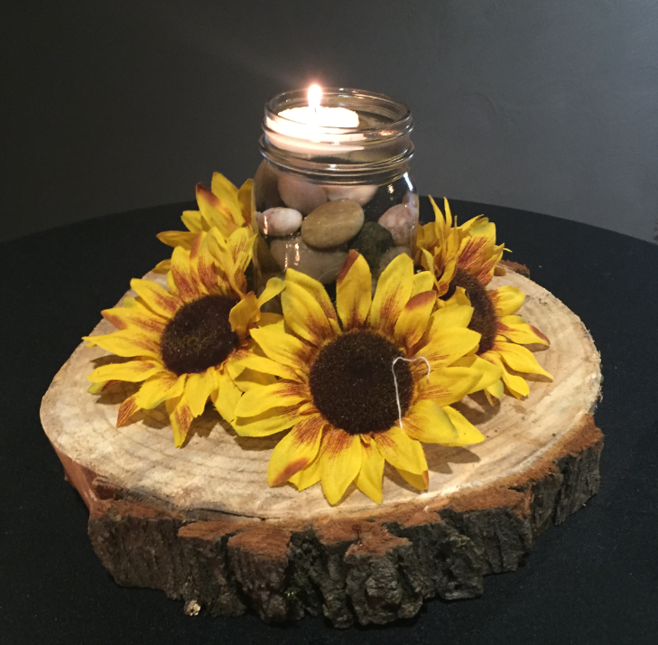 Small Mason Jar Filled With Neutral Stones Water And A Floating Candle Sunflower Ring Around The Base On Log Round