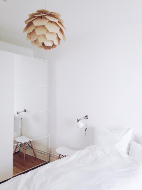 Superhelles Schlafzimmer mit Design-Lampe und weißen Bettbezügen