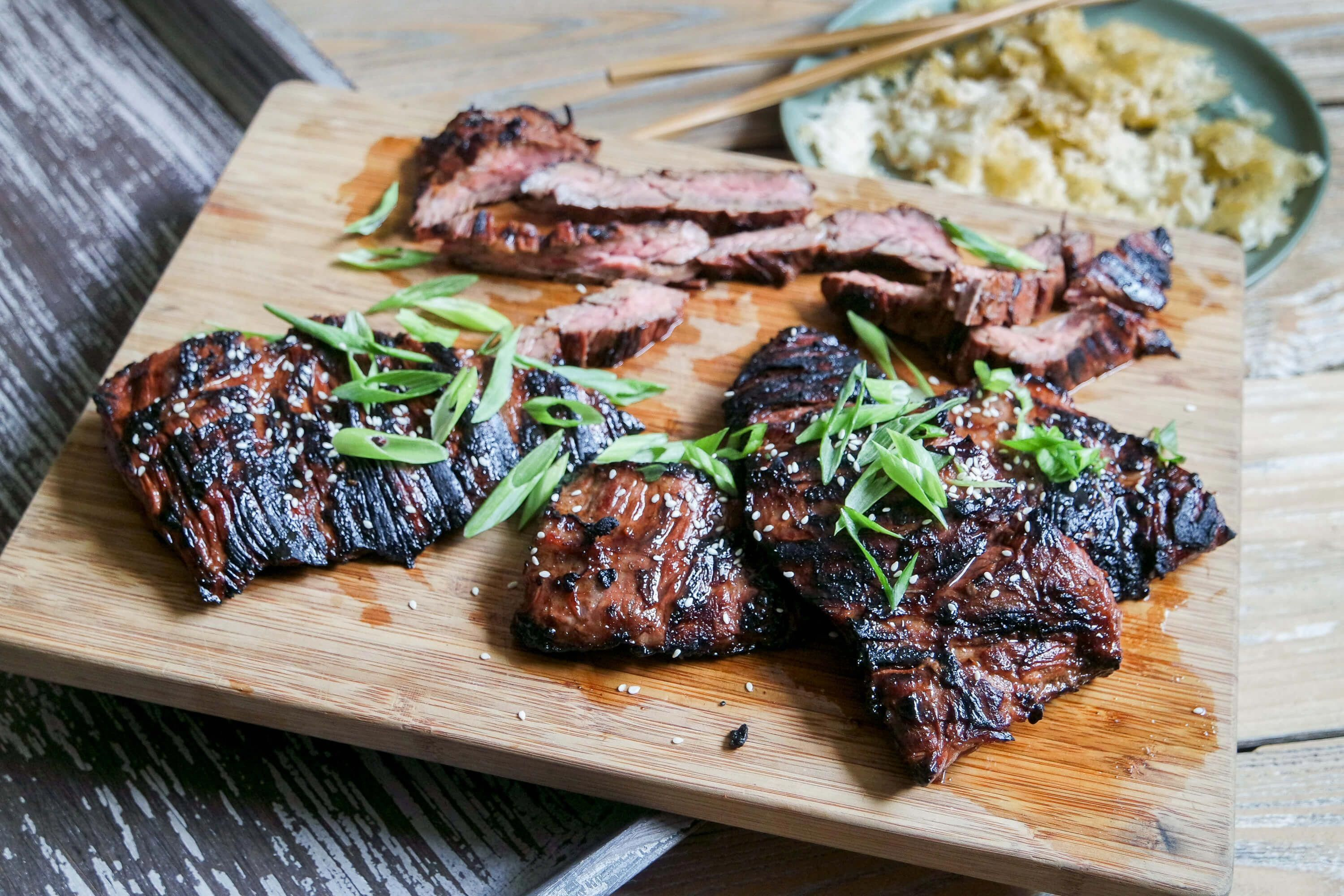 A soy and sriracha marinade lends a salty, umami punch with a hint of sweetness. Paired with crispy rice, this Asian Marinated Grilled Skirt Steak is hard to beat. #grilledsteak #marinadeforskirtsteak