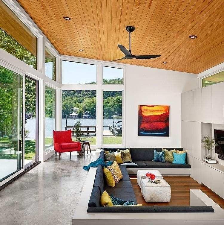 Salon design avec sol en béton ciré lambris plafond en bois et déco en couleurs
