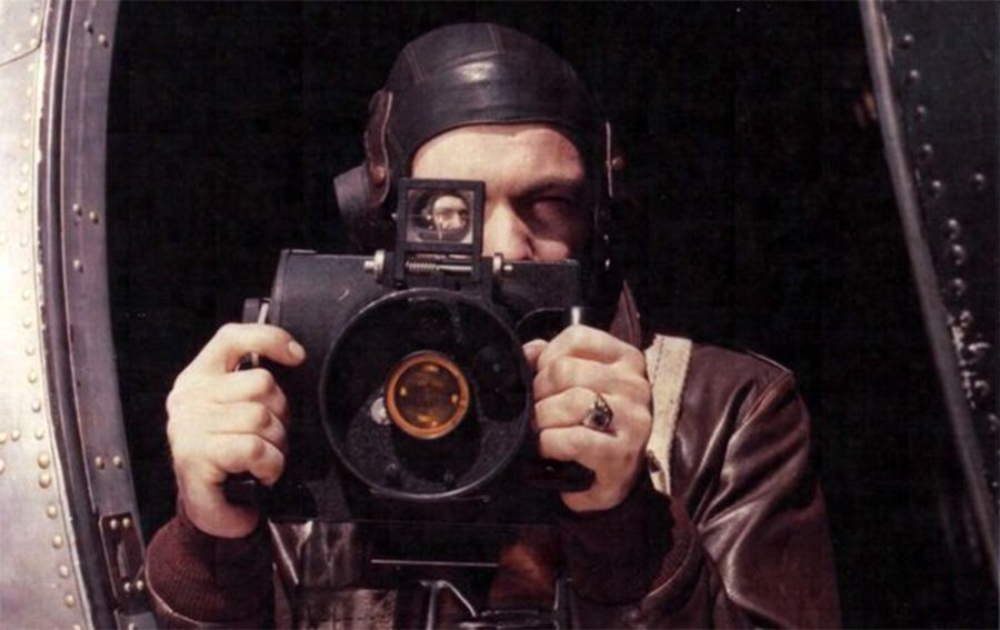 S/Sgt Brush poses with K-20 camera at waist window of B-17.