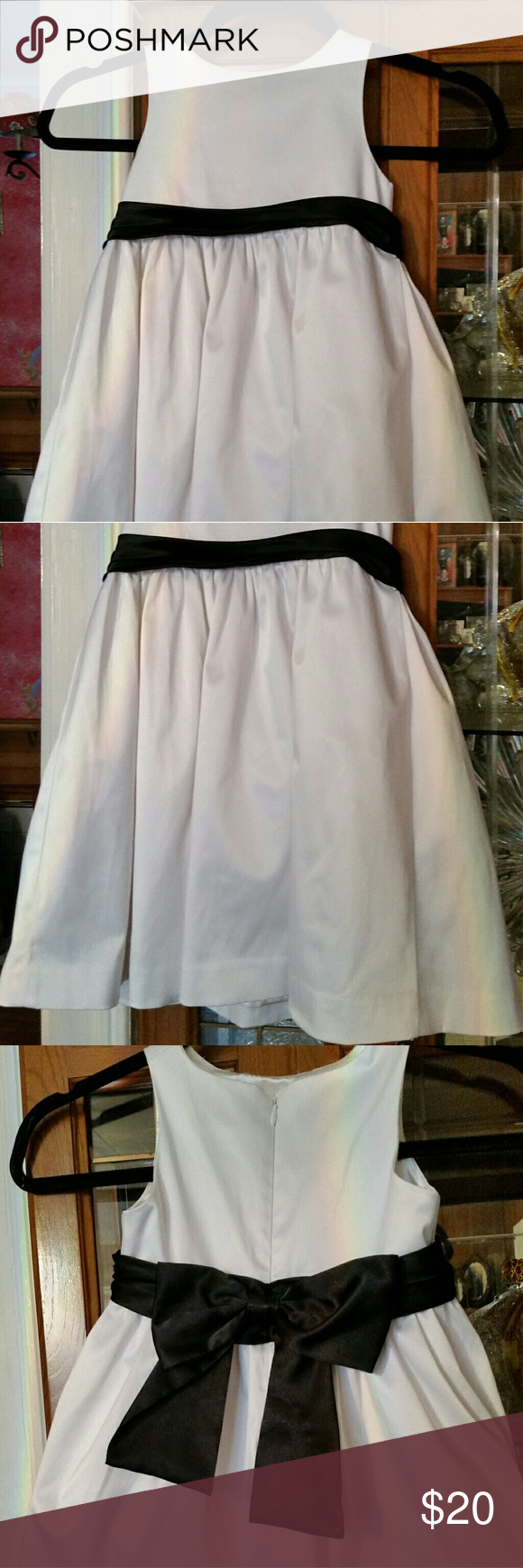 Isaac Mizrahi Little Girl's White Dress Little Girl's white dress with black sash with bow that snaps on back.  It is dry clean only so I ironed it, but did not have it dry cleaned.  Cute little dress that can be used for flower girl dress or special occasion.  There are no stains.  Discoloration is from my light. Isaac Mizrahi Dresses Formal