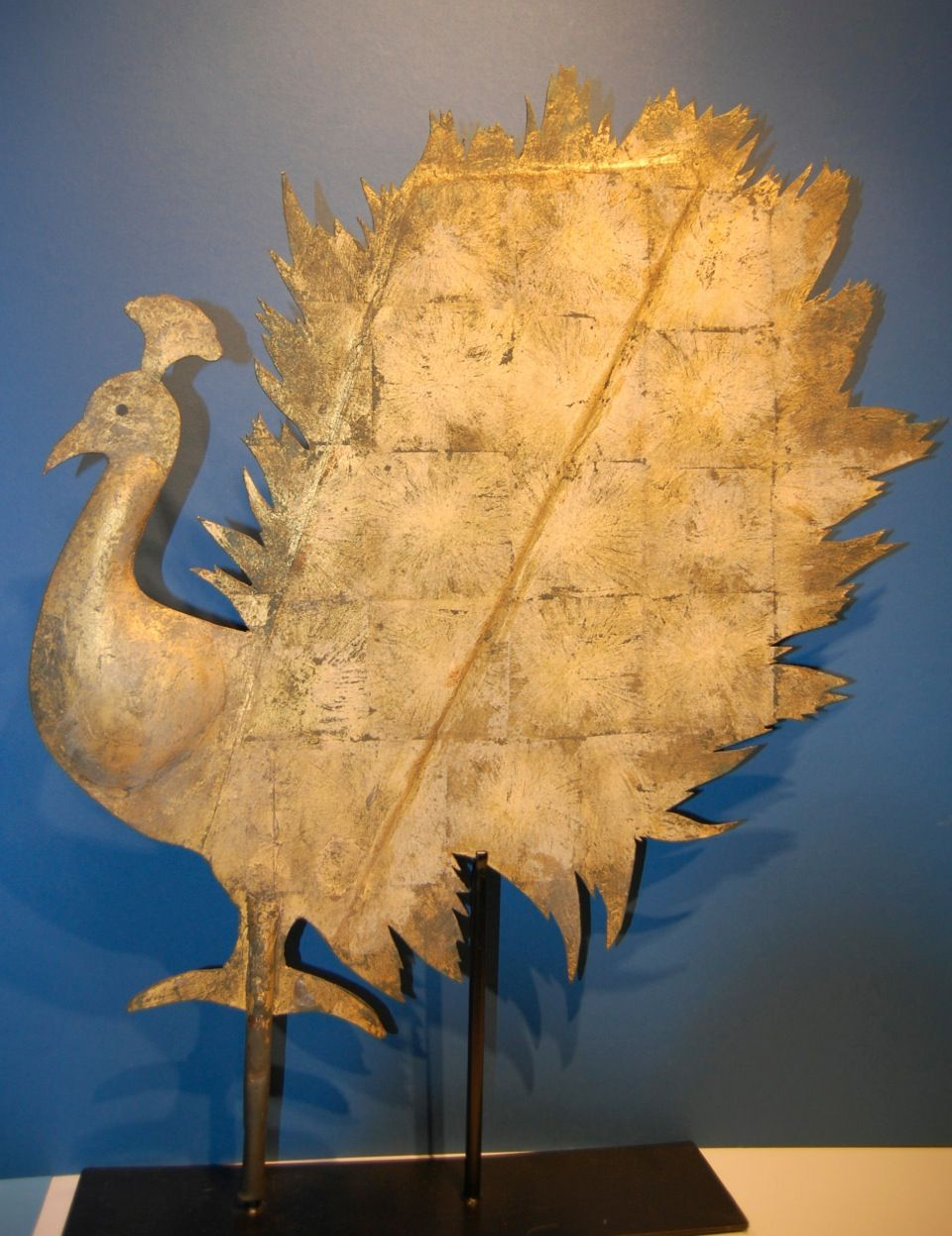 """Fabulous Peacock Weathervane by the Jewell Co.c 1865-1875. Cast zinc body with a very heavy gauge copper tail. The fantastic tail is highlighted by the worn squared gold leafing. It retains several patinas but has heavy elements of a second gold leafing. This weathervane surfaced about 25-27 years ago from a farm in Central Maine and has been in a private family collection ever since. Measures 21"""" ht x 26"""" front to back. Museum mounted. Call Jeanne for pricing on 845.505.1147"""