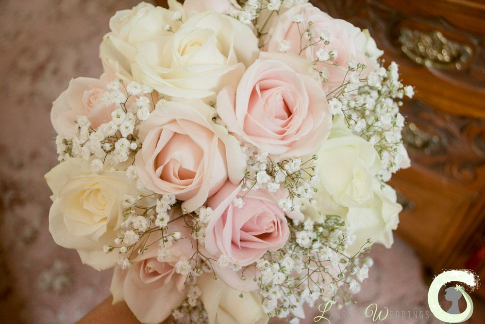 Hand tied bouquet of blush pink and ivory roses with ...
