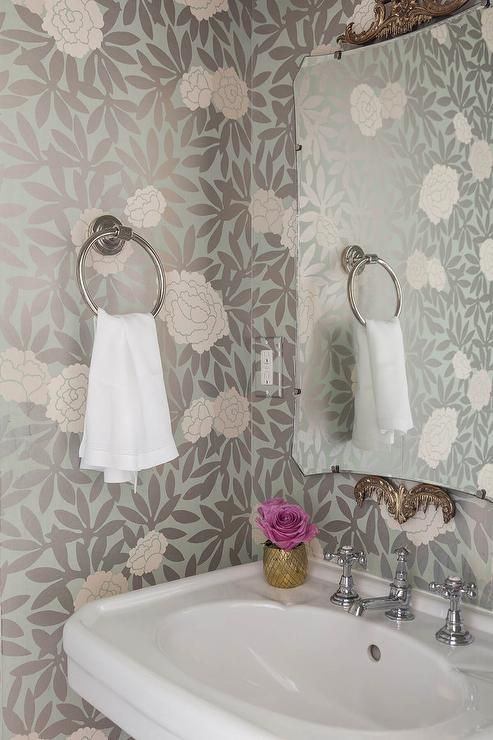 Sophisticated powder room features walls clad in pink and