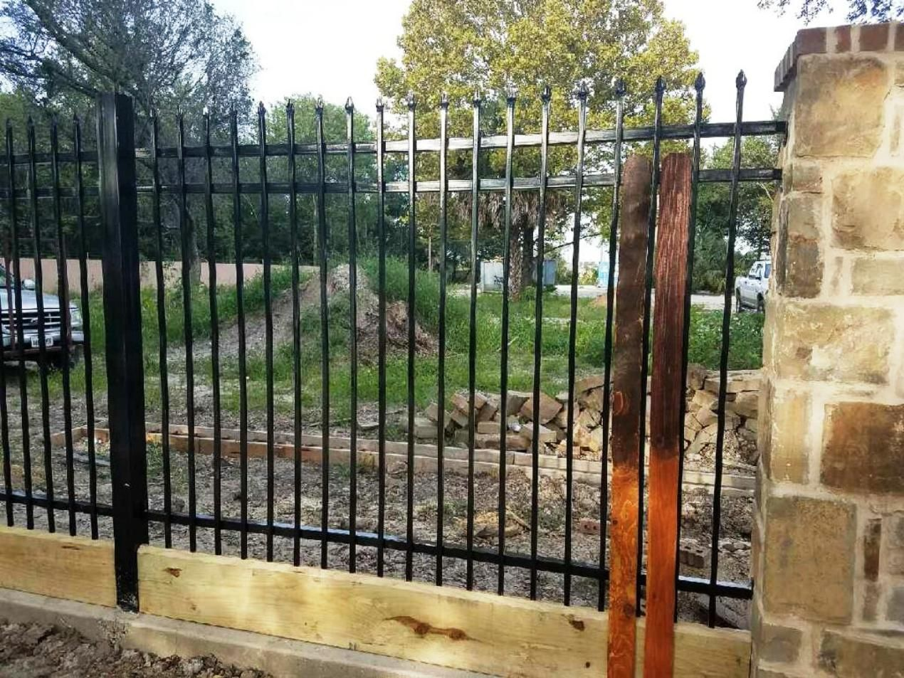 Custom Iron Fence With Wood Panel Slates For Added Privacy And Beautiful Stone Columns Expert Installation For Iron Fence Iron Fence Gate Wrought Iron Fences