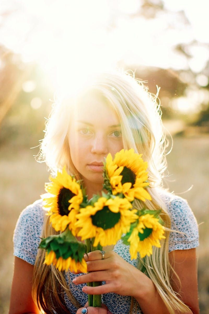 Free download of this photo: https://www.pexels.com/photo/female-smelling-sunflower-in-sunny-day-227716/ #woman #field #flowers