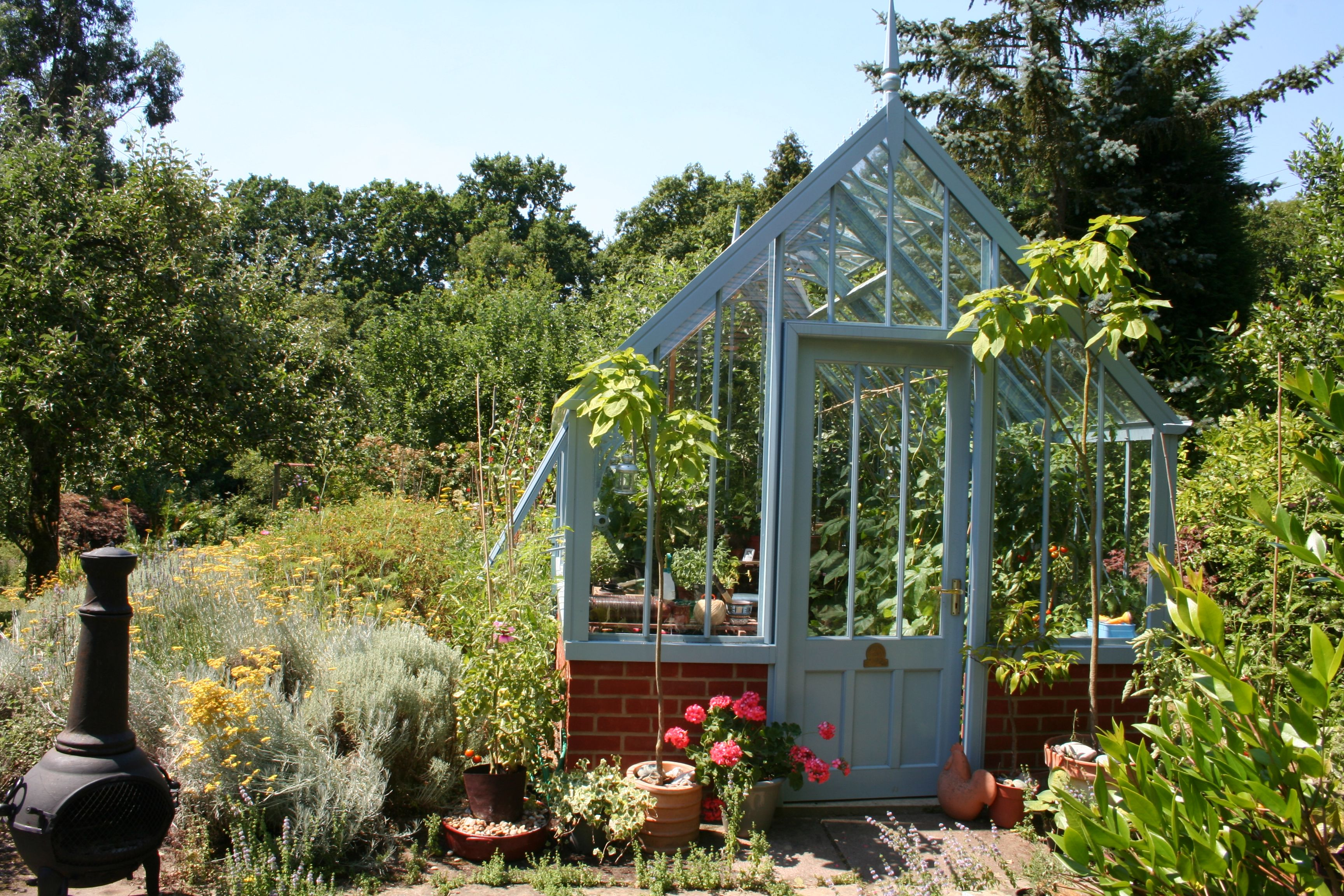 Blue greenhouse. Not for everyone, but looks bright all year round. Mediterranean feel to the garden too. www.alitex.co.uk