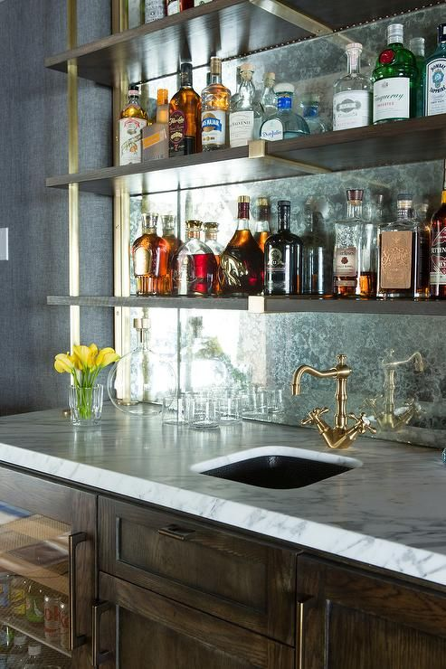 A rustic wet bar boasts dark stained oak cabinets fitted with a glass door beverage fridge topped with white marble lined with a bar sink and an antique brass vintage faucet under stacked wood and brass shelves lining an antiqued mirrored backsplash.
