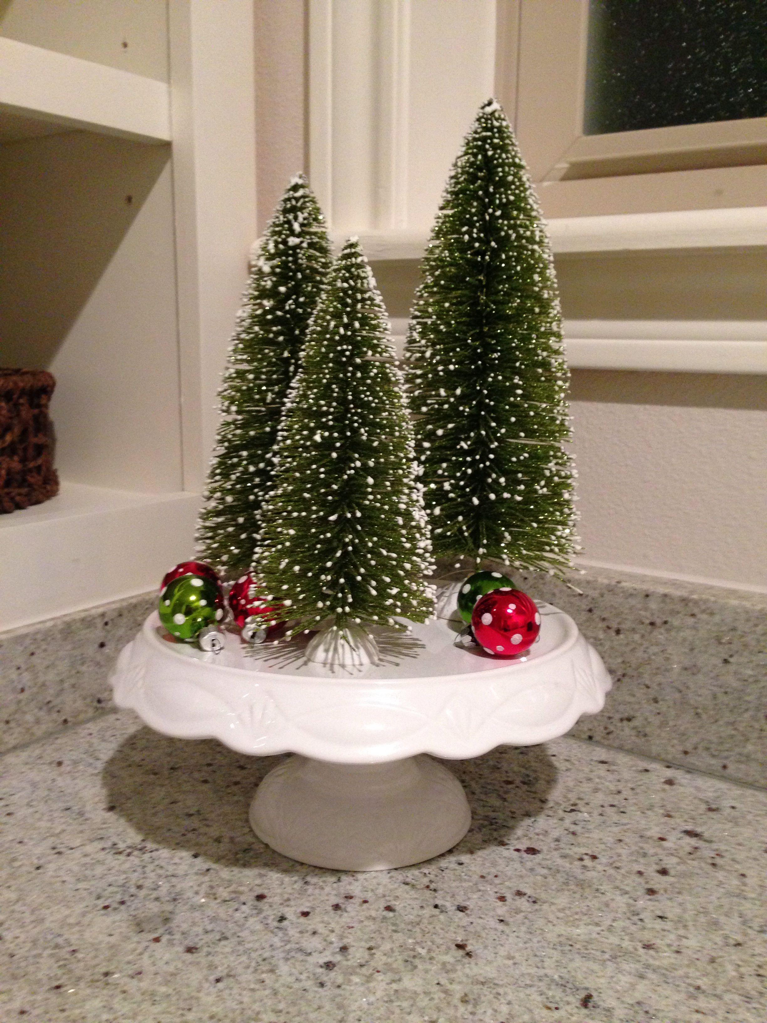 A white cake stand three bottle brush trees 5 mini