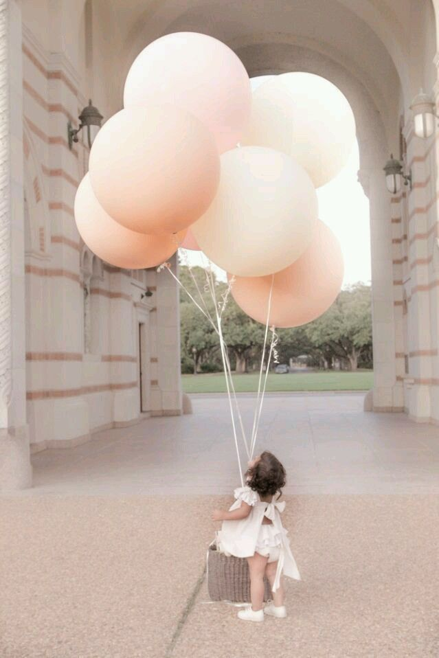 Cute shot of baby looking up at balloons. Love the color of the balloons and the shape.