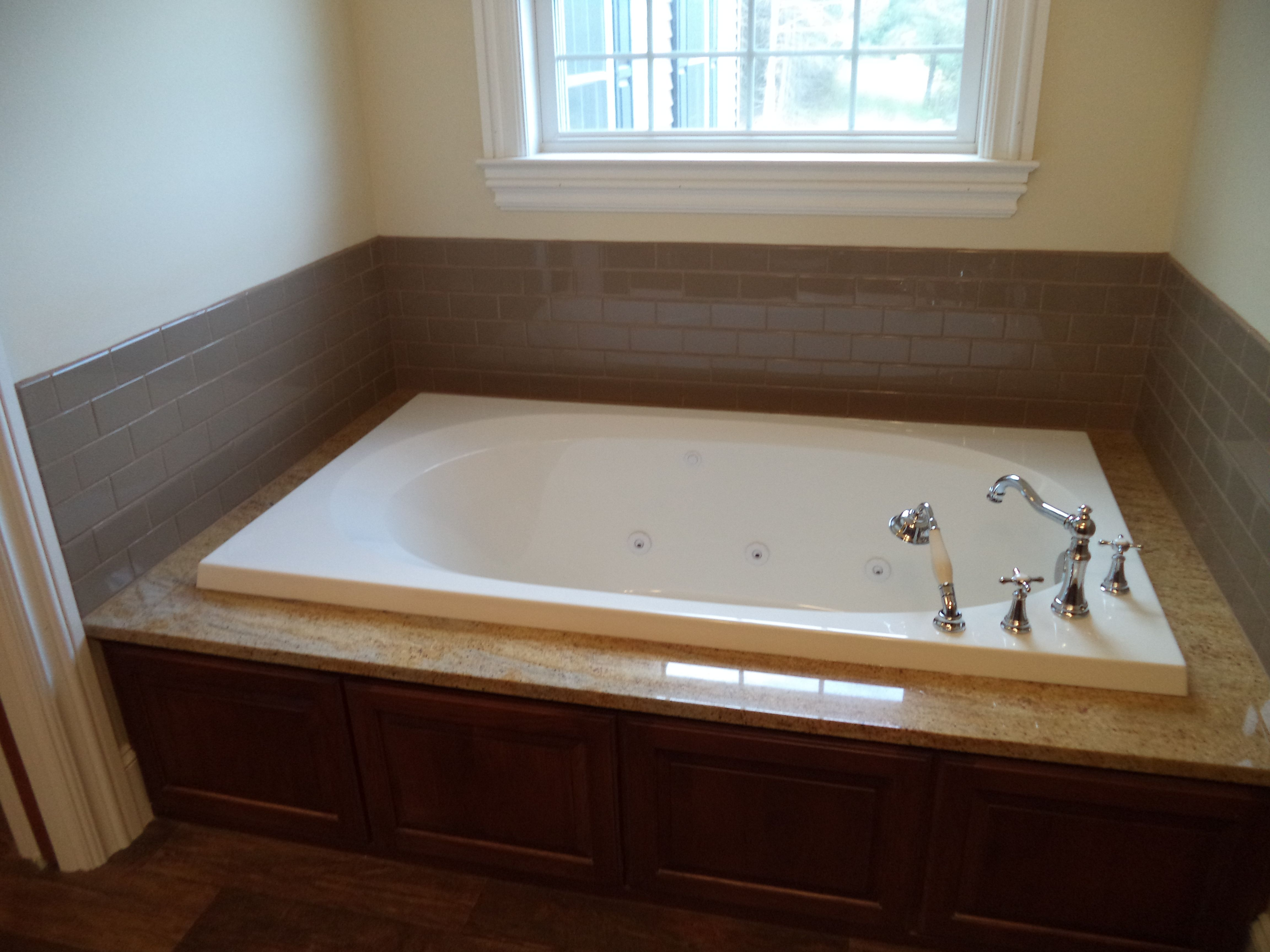 Whirlpool Tub With Gold Granite Deck Ceramic Tile Surround Wooden Access Panel And Moen Weymouth Hardware 15 88