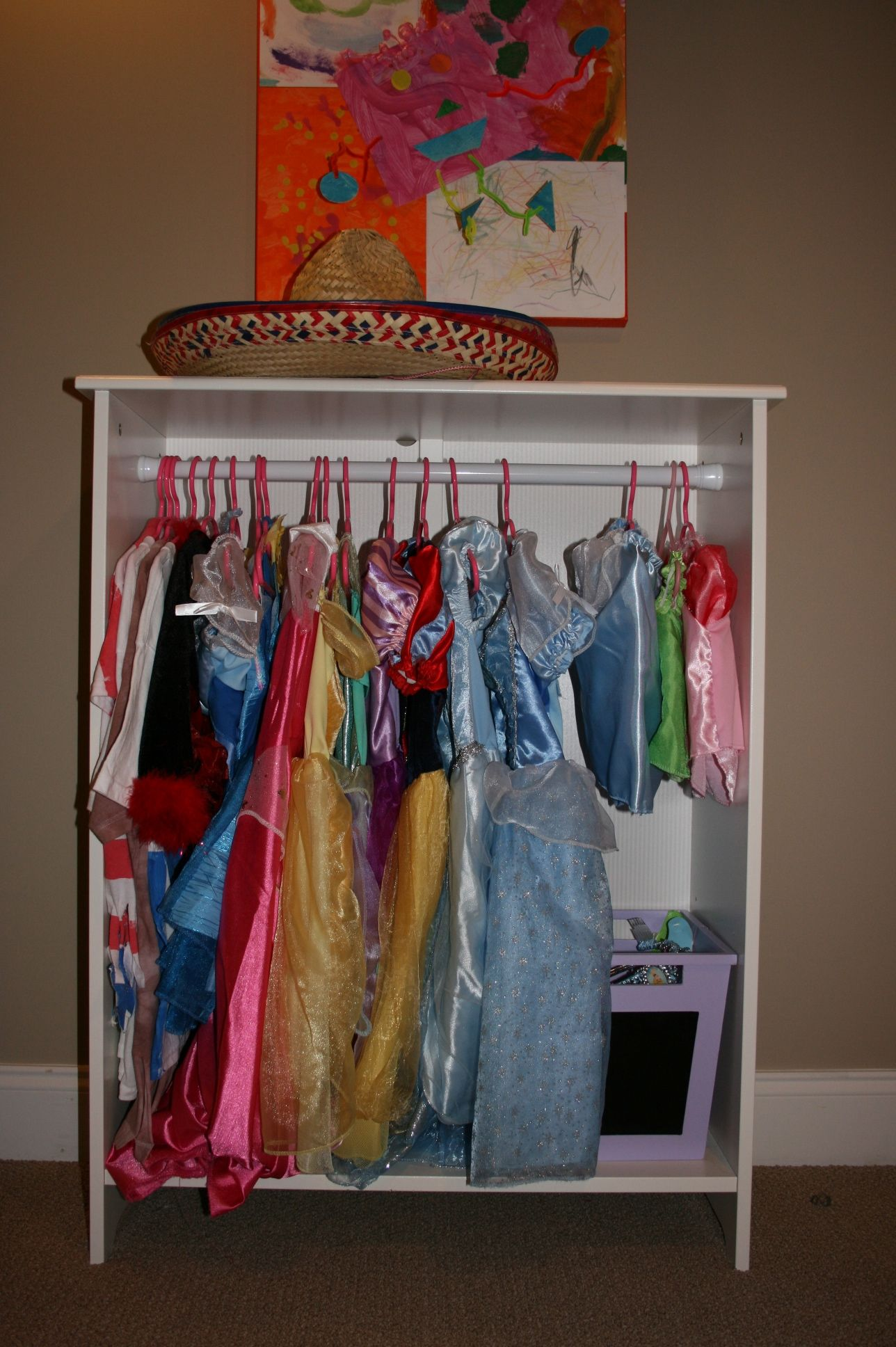 ikea bookshelf and tension rod = closet for dress up clothes. I'm doing the mini version of this for my son's dress-up collection. My hope is he uses his dress-up more when it's on display... Right now it's all in a plastic box and I'm not sure he even knows it's there.