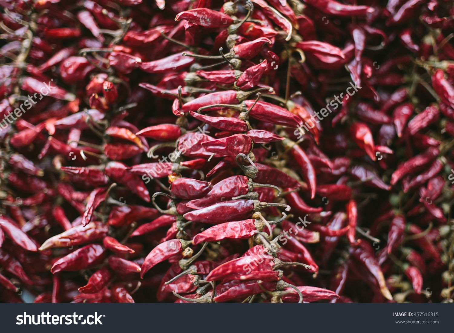 Whole Red Chili Peppers On The Market Hanging. Background