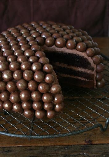 chocolate cake with whoppers     4 eggs  200g sugar  200g butter (room temperature)  pinch of salt  200g self-raising flour  100g cocoa powder  3 tbsp baking powder  1/2 tbsp all spice  pinch of cinnamon  4 tbsp rum  4 tbsp milk  4 packs of Maltesers  edible gold powder    For the butter cream:  200g butter  100g icing sugar  300g chocolate custard
