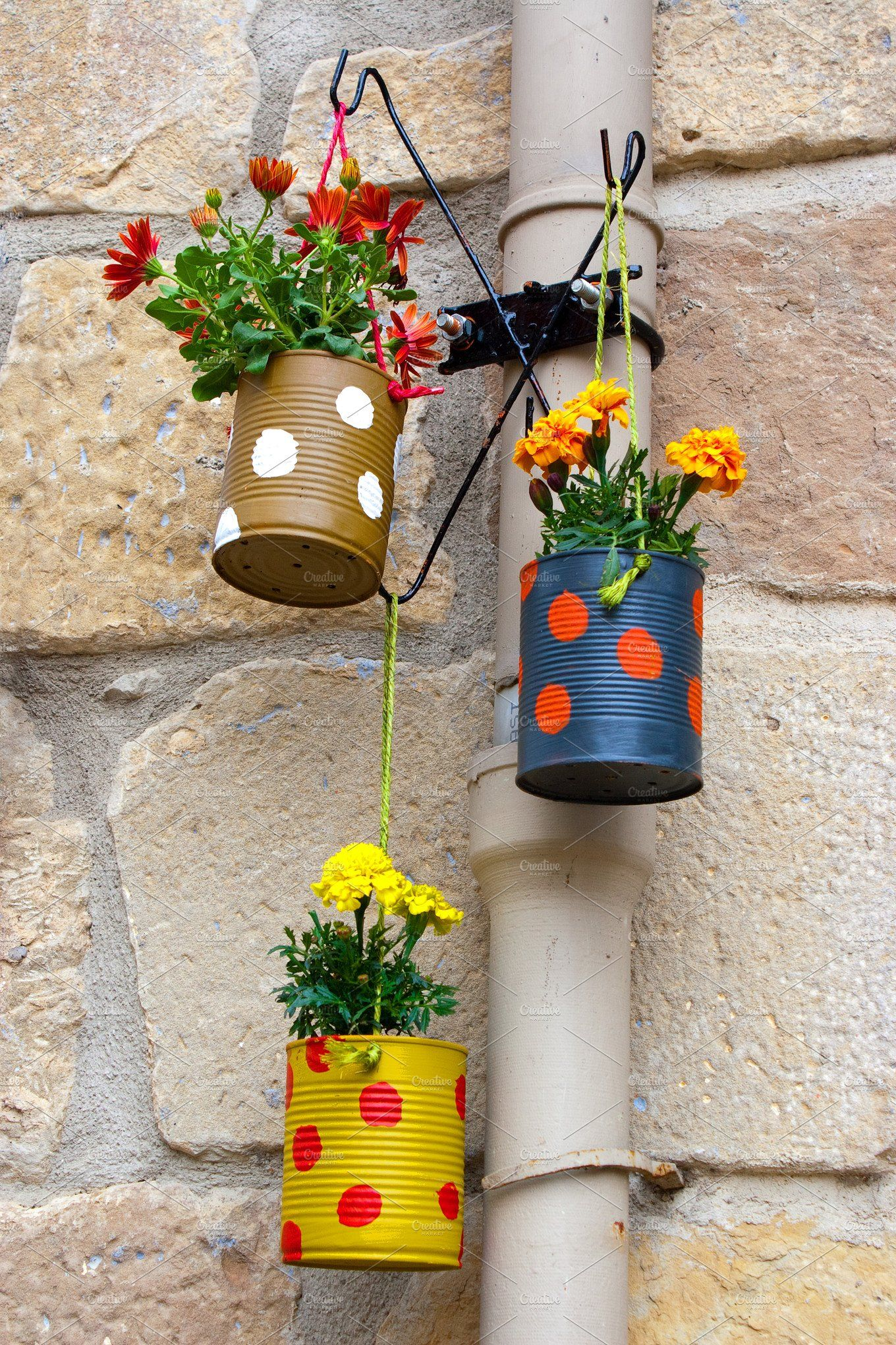 Hanging flowerpots made with cans in the street.