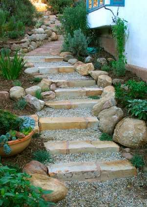 Natural stones steps with gravel, and lined with medium boulder stones, and plants.