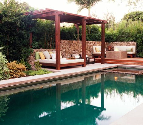 Outdoor poolside lounge bed with pergola. Rob Steiner Gardens