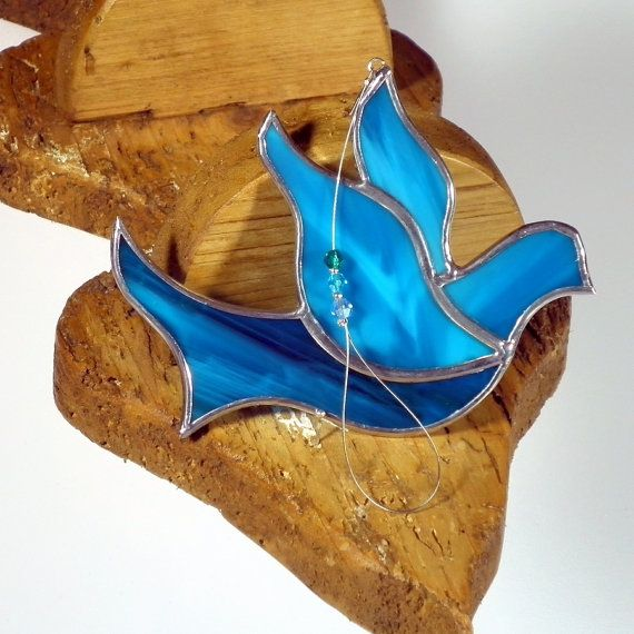 This pretty Dove has been made using the Tiffany method from high quality stained glass in very deep shade of aqua. All decoration measures approximately 3.5in per 3.5in (9x9cm). It is hanging on a tiger tail wire with few swarovski beads. The Solder is well polished for extra