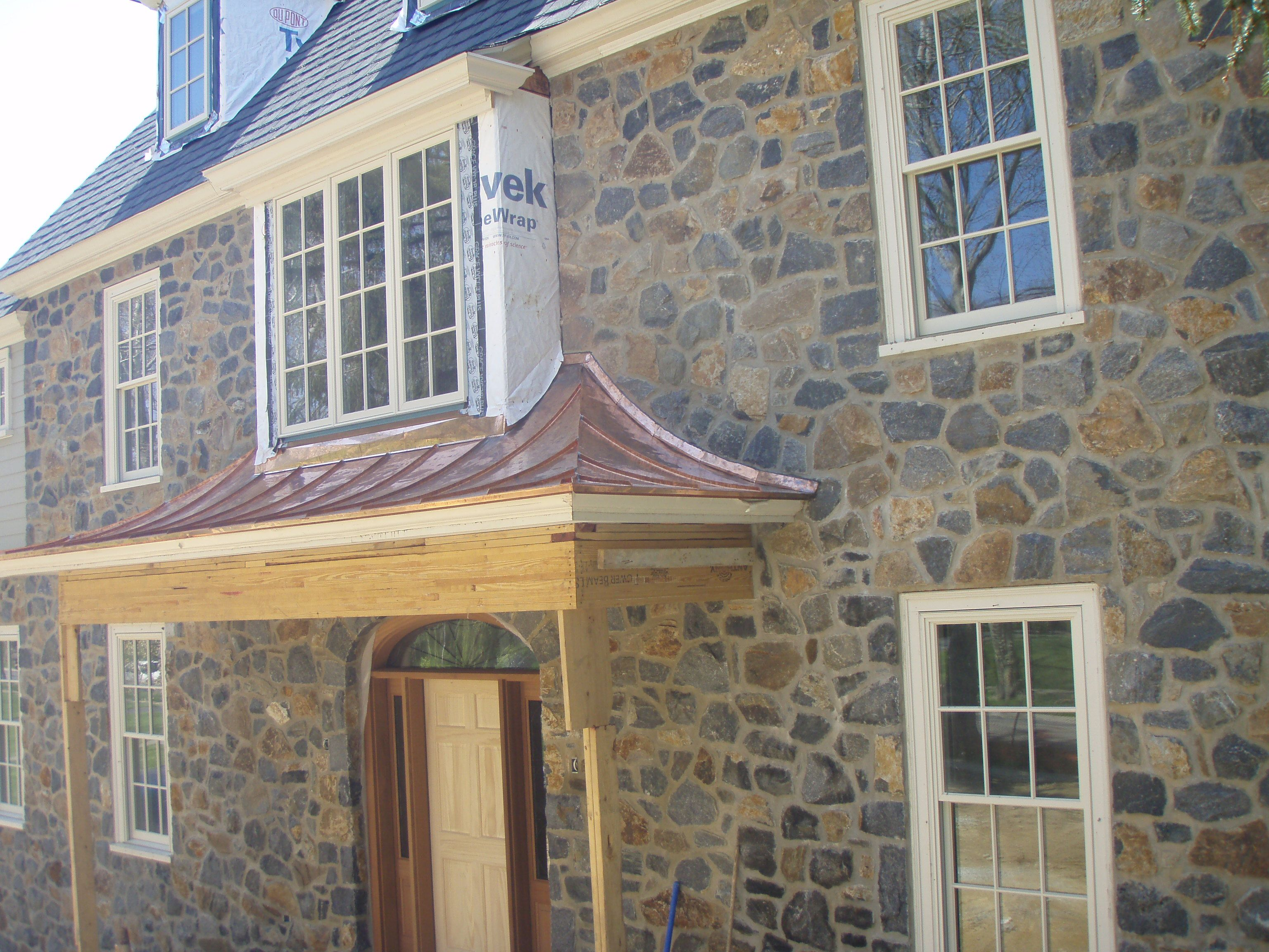 Concave standing seam copper roof over door way metal for Metal hip roof