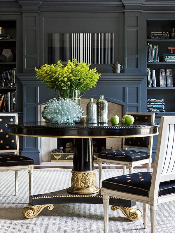 Love the blue-gray color in this den. The darker hue is balanced by gray and cream striped rug underfoot.