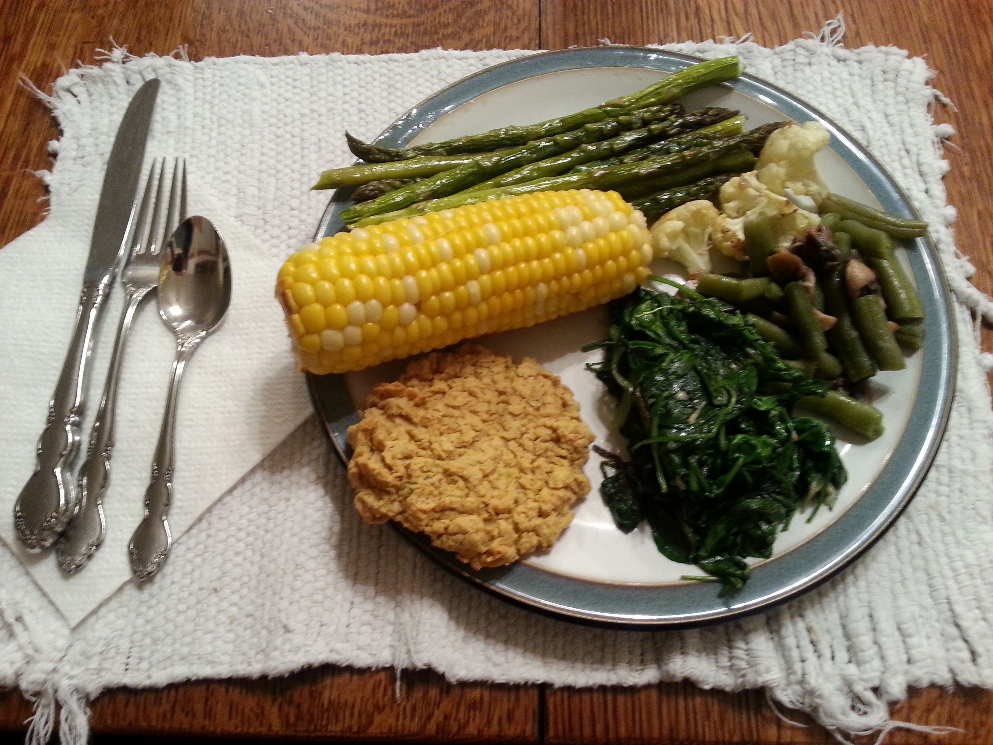 TQI Meatless Dinner: chickpea patty, corn on the cob, greens, green beans with mushrooms, roasted cauliflower, asparagus.