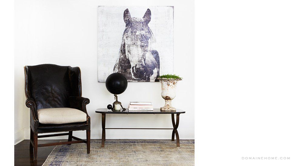 wingback chair upholstered in weathered black leather; equestrian-themed giclée print hanging over an indoor garden themed vignette; muted Persian rug
