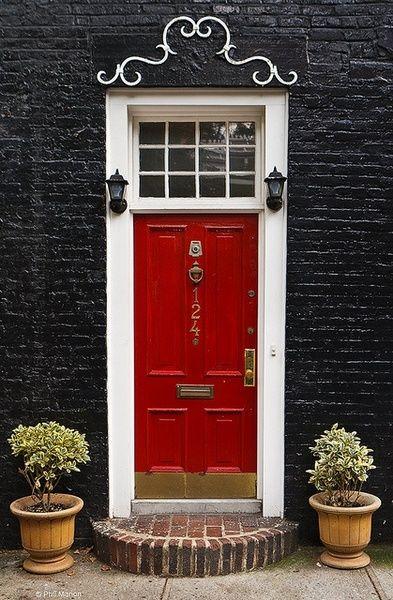 a red door and black bricks