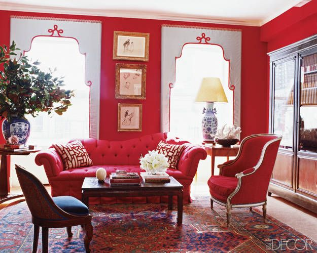 A Glamorous Renovation The custom-made sofa and throw pillows are covered in a Clarence House linen and velvet, respectively, the Oushak rug is antique, and the Louis XVI-style bergère is from Todd Alexander Romano; the porcelain vase, Chinese table lamp, and antique cocktail table are all from John Rosselli Antiques and Decorations. The trio of artworks is by Jean-Louis Forain, the window treatments are of a Kravet silk with Lee Jofa silk trim, and the walls are sheathed in red felt.