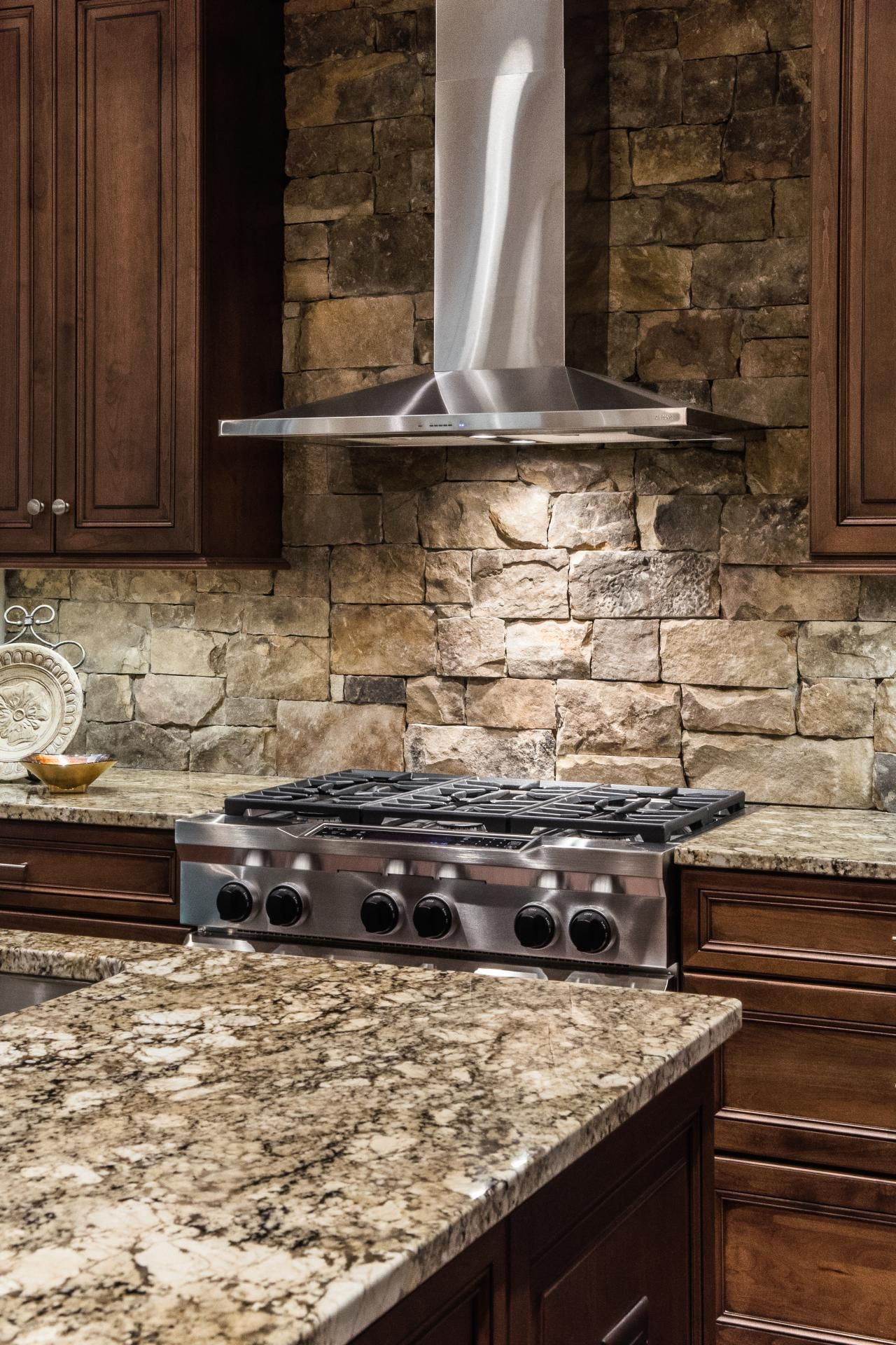 stacked stone kitchen backsplash copper undermount sink a stainless steel range hood is sleek contemporary counterpoint to the