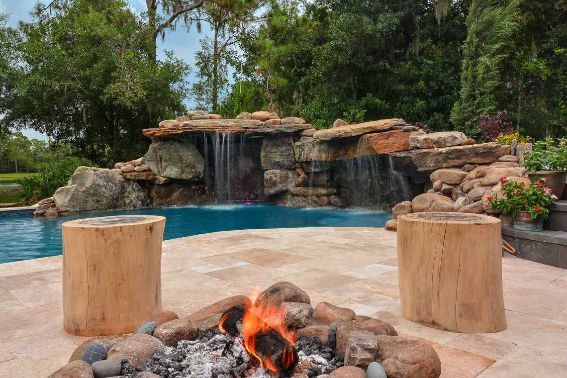 Sitting By The Poolside Fire Pit With Two Log Seats And A View Of The Backyard Pool Waterfall Insane Pools Fire Pit Pool Waterfall