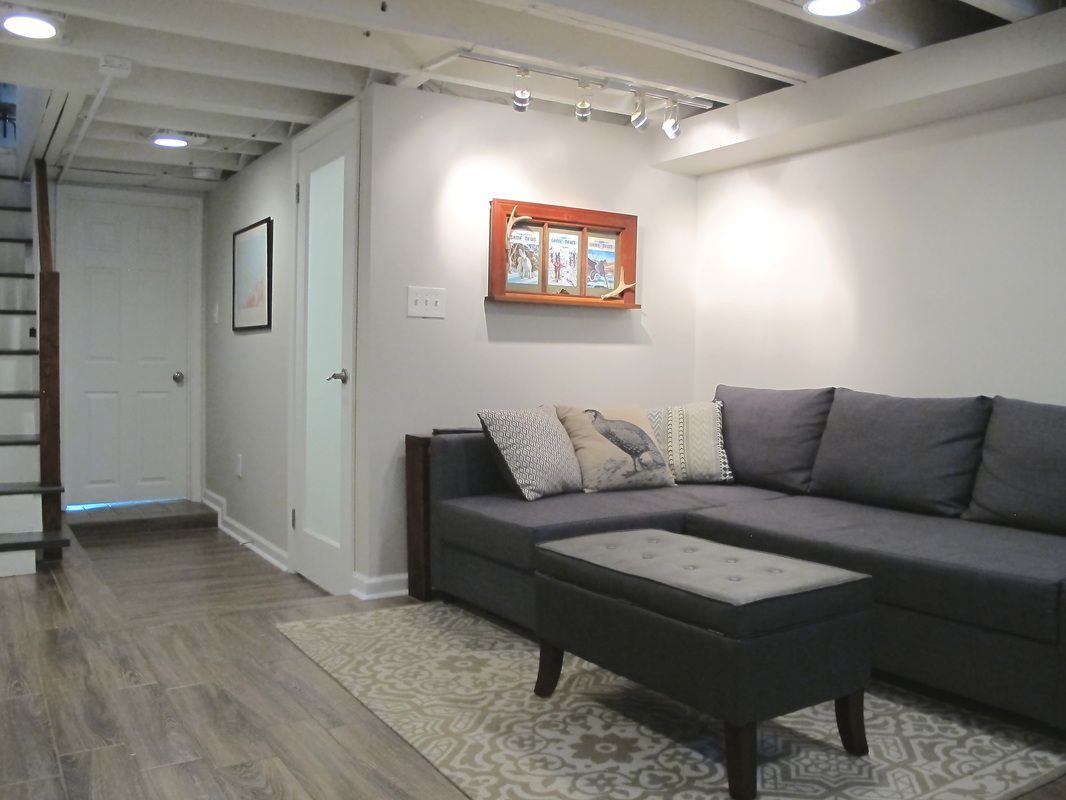 cozy chic basement reno with exposed painted joists & wood tile