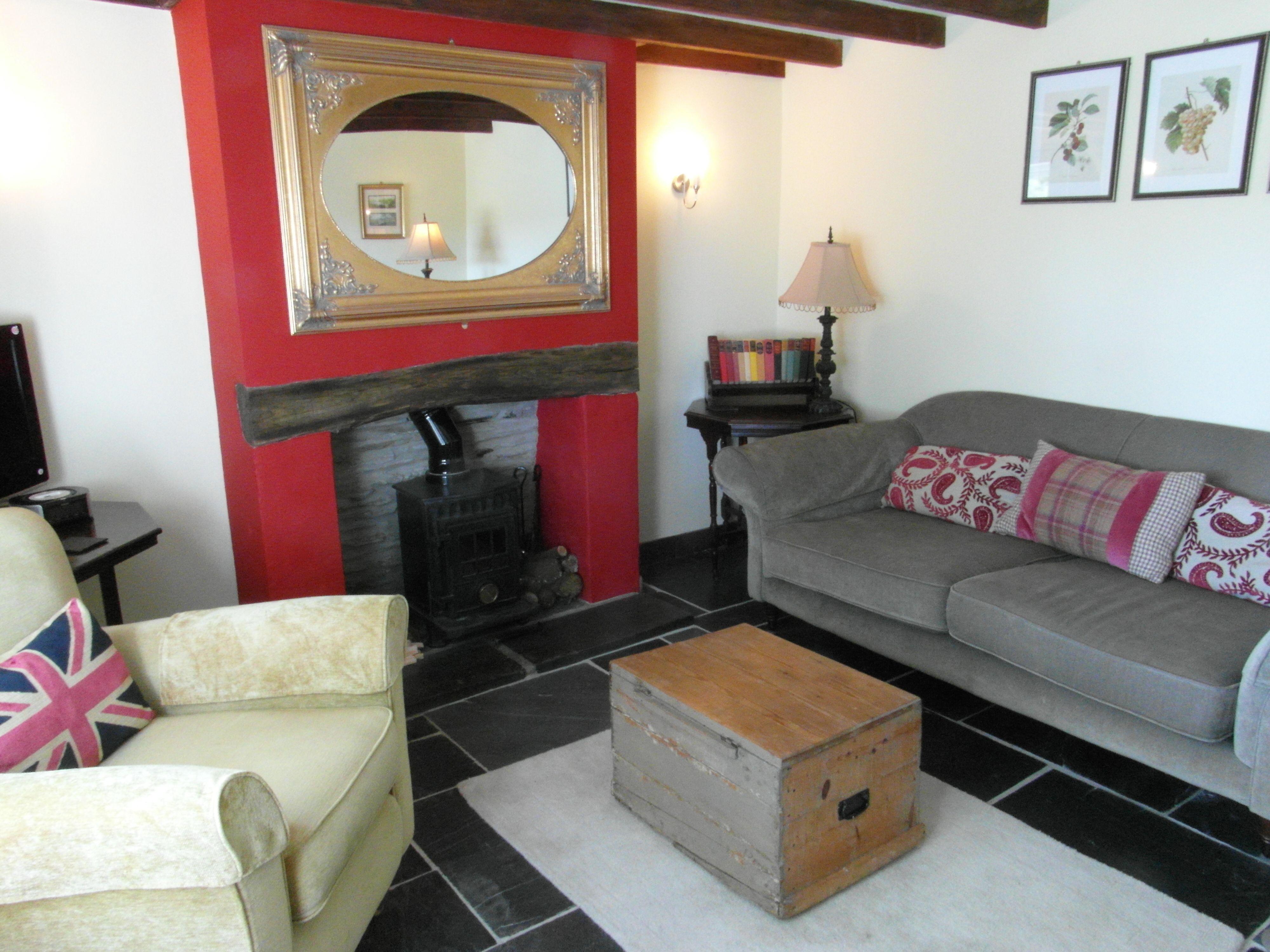 Cottage sitting room fy sofa chairs toasty log burner TV DVD