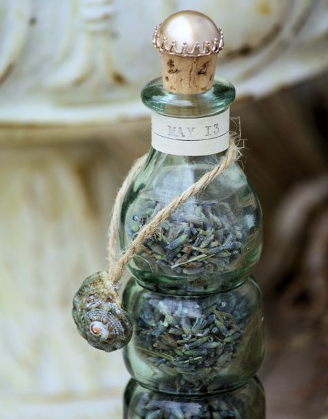 bottle embellished with vintage items and bits of the sea