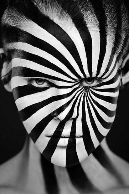 Striking series of portraits of models with various designs painted onto their faces the faces are either painted completely black or completely white