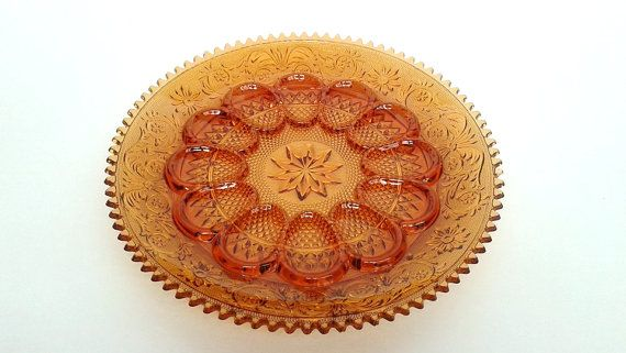 "This beautiful vintage amber glass deviled egg platter or plate is in excellent condition with no chips or cracks and measures approximately 12"" in diameter. It features detailed scrolling designs and geometrical patterns and it has a ten pointed star in the center."