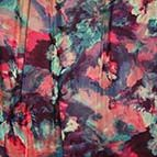 This silk printed chiffon shows an abstract design that blends in different shades of red and green.54