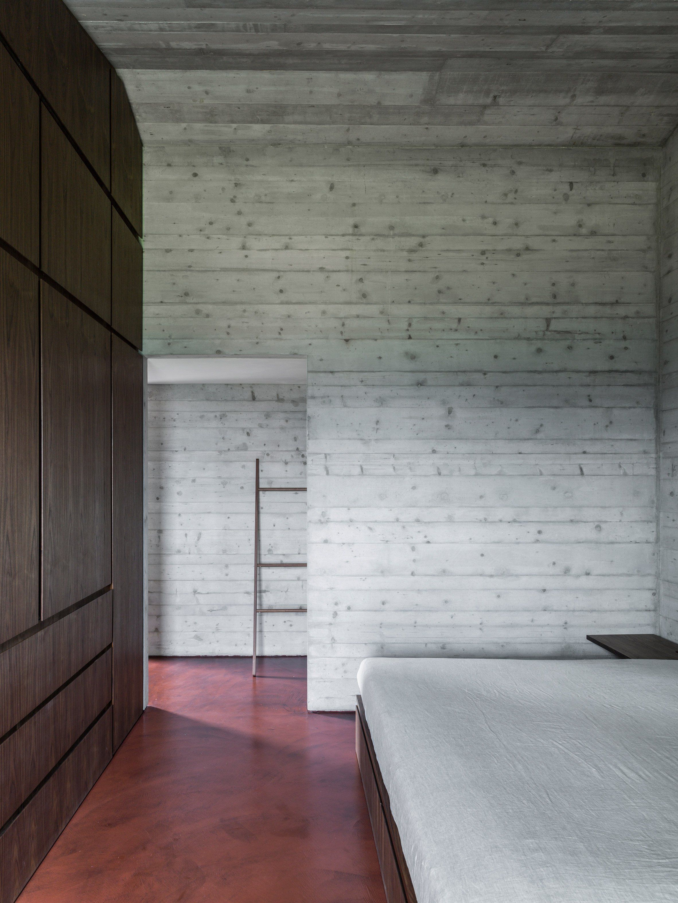 Grey concrete walls red concrete floor and walnut storage unit rural italian residence by gga architects